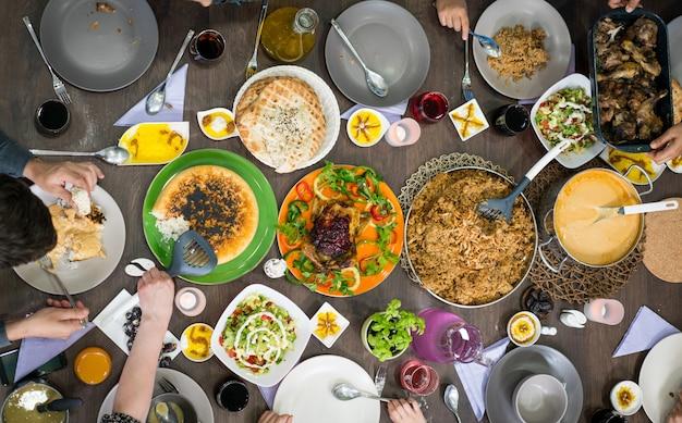 Vista superior da família e amigos comendo comida na mesa