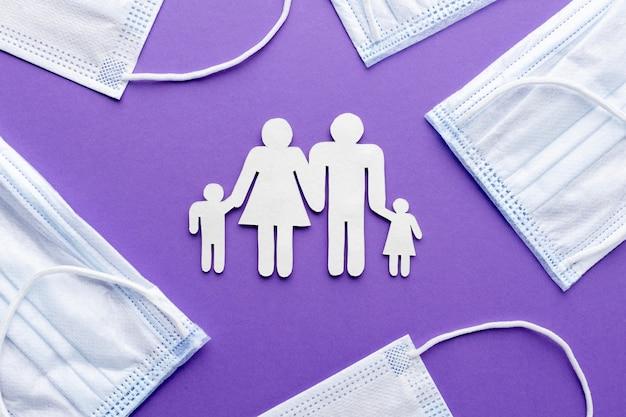 Vista superior da família feita de papel com máscaras médicas