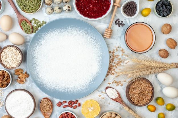 Vista superior da farinha branca dentro do prato com sementes de nozes e ovos na massa branca, foto cor de comida, geléia de nozes