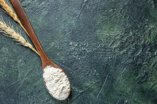 Vista superior da farinha na colher de pau na mesa escura
