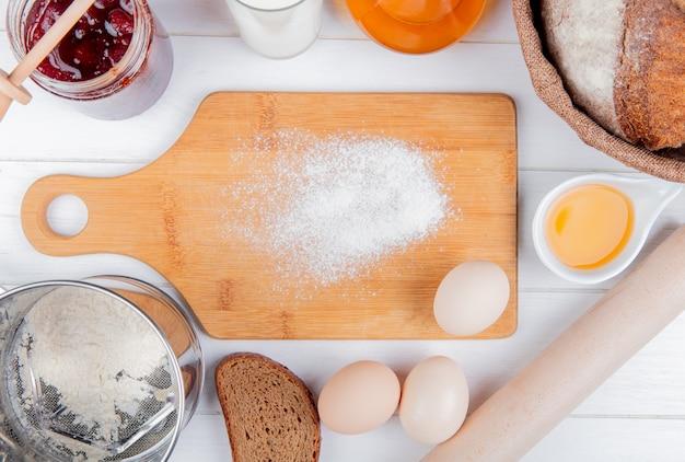Vista superior da farinha na tábua com geléia de morango leite manteiga espiga e centeio pães ovos e rolo ao redor em fundo de madeira