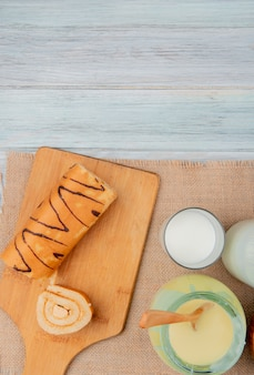 Vista superior da fatia de rolo e rolo cortada na tábua com leite leite condensado de saco na mesa de madeira com espaço de cópia