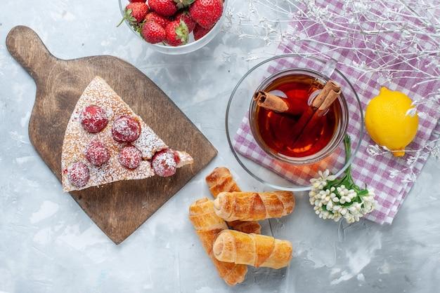 Vista superior da fatia do bolo com pulseiras doces de morangos vermelhos frescos e chá na mesa leve, biscoito de biscoito doce assado