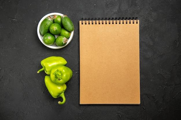Vista superior da feijoa verde fresca com pimentão verde e bloco de notas na superfície escura.