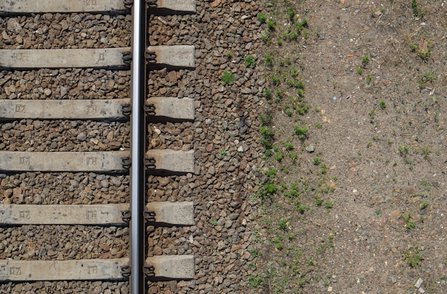 Vista superior da ferrovia, lay flat. parte dos trilhos para trens. vista aérea de uma ferrovia de um drone. fundo com espaço para texto. trilhos de ferro brilhante e travessas de concreto.