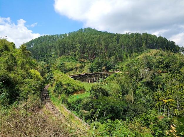 Vista superior da ferrovia na selva e da famosa ponte de nove arcos