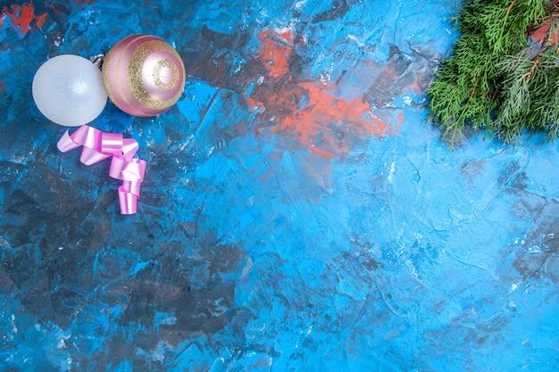 Vista superior da fita rosa das bolas da árvore de natal na superfície azul-vermelha