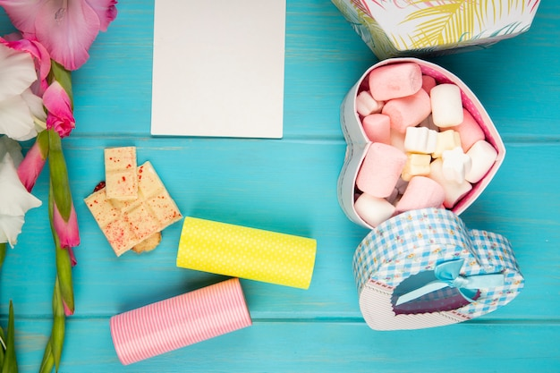 Vista superior da flor de gladíolo cor rosa com rolo de fita adesiva, folha de papel branca, barra de chocolate branca e caixa de presente colorida cheia de marshmallow na mesa azul