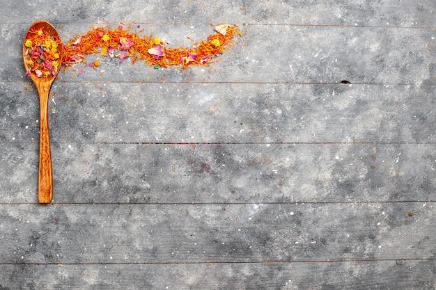 Vista superior da flor de laranjeira seca dentro de uma colher de pau em um espaço rústico cinza