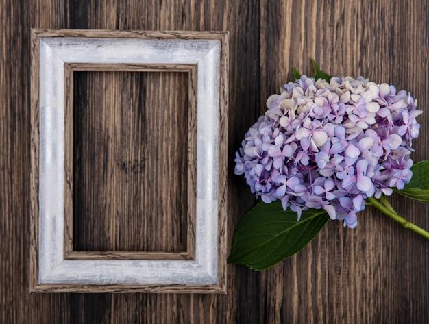 Vista superior da flor e moldura em fundo de madeira com espaço de cópia