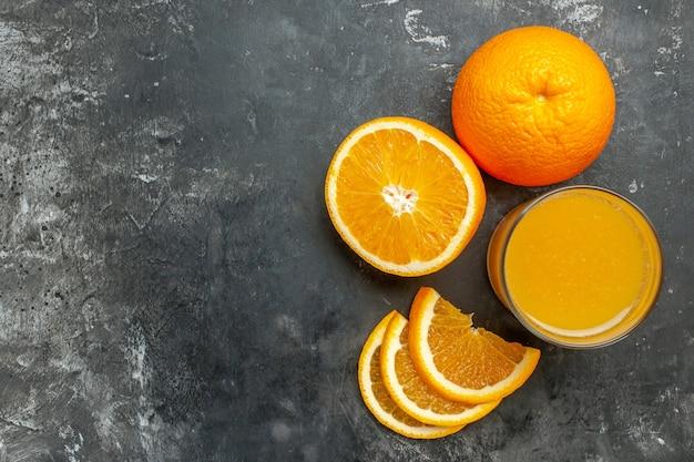 Vista superior da fonte de vitamina cortada, laranjas frescas inteiras e inteiras e suco em fundo cinza