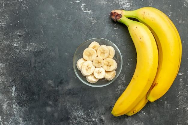 Vista superior da fonte nutricional pacote de bananas frescas e picadas em um pote de vidro em fundo cinza