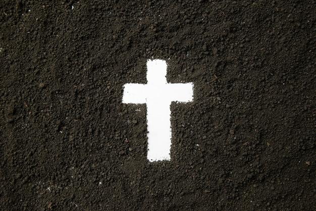 Vista superior da forma de cruz branca com solo escuro