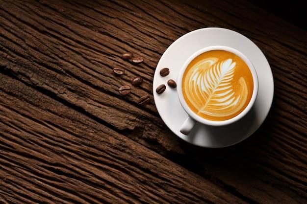 Vista superior da forma de uma xícara de café com leite e grãos de café na velha mesa de madeira