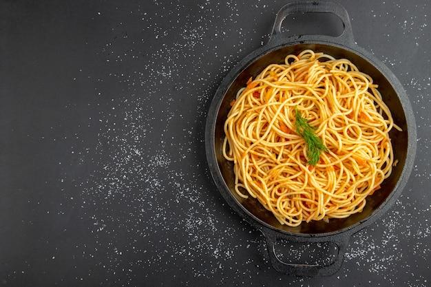Vista superior da frigideira de espaguete em fundo escuro