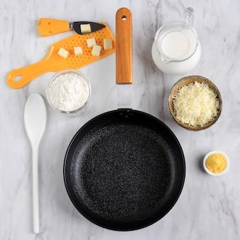 Vista superior da frigideira, queijo, farinha, leite, preparação de molho bechamel (molho branco para massas) ingredientes na mesa de mármore branco