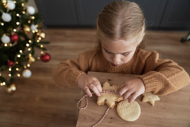 Vista superior da garota empacotando biscoitos para o papai noel