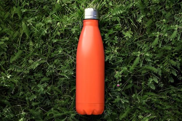 Vista superior da garrafa de água térmica de aço reutilizável na grama verde, cor de lava exuberante.