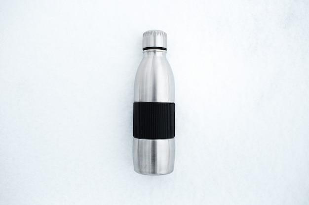Vista superior da garrafa de água térmica de aço reutilizável na neve.