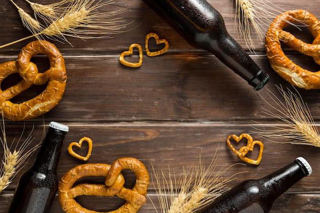 Vista superior da garrafa de cerveja com pretzels e trigo