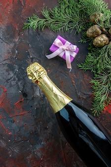 Vista superior da garrafa de champanhe com presente em cor escura bebida alcoólica foto festa de ano novo