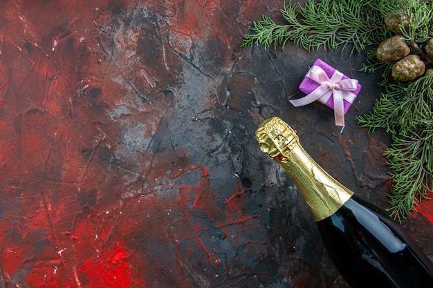 Vista superior da garrafa de champanhe com presentes em cor escura bebida álcool foto espaço livre festa de ano novo