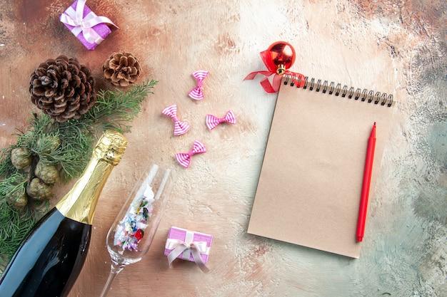Vista superior da garrafa de champanhe com presentinhos e bloco de notas na luz de natal com álcool para presente de ano novo