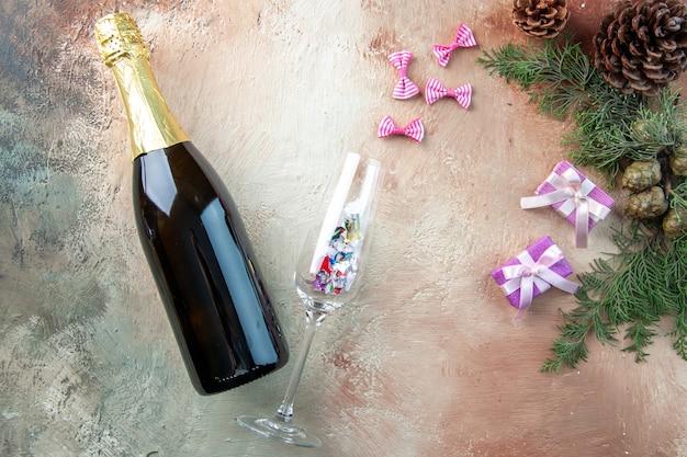 Vista superior da garrafa de champanhe com presentinhos na luz do presente de natal foto ano novo álcool colorido
