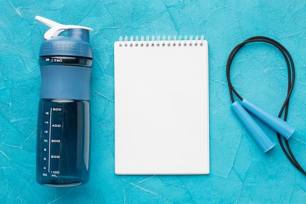 Vista superior da garrafa de fitness e bloco de notas em branco