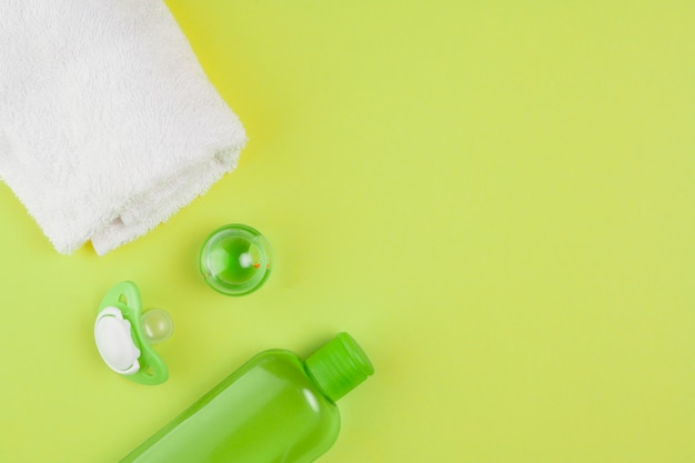 Vista superior da garrafa de óleo com toalha e chupeta para chá de bebê