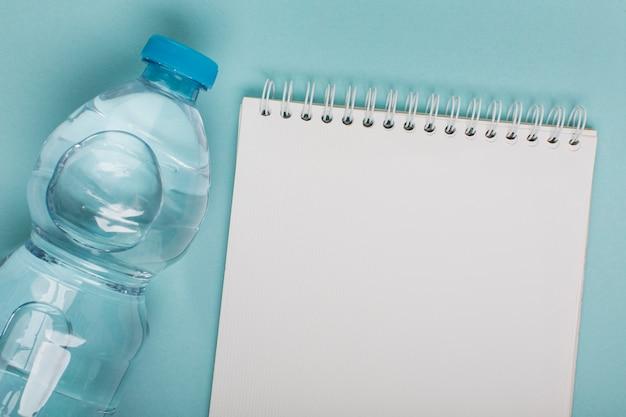Vista superior da garrafa de plástico com água e bloco de notas de espaço