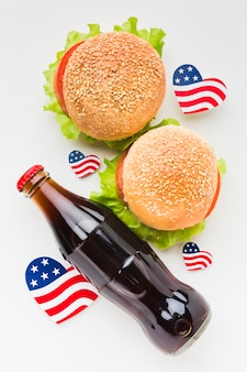 Vista superior da garrafa de refrigerante com hambúrguer e bandeiras americanas
