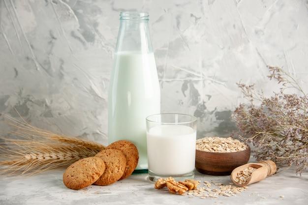 Vista superior da garrafa de vidro e do copo cheio de leite na bandeja de madeira e biscoitos colher aveia em pote marrom espeto na mesa branca sobre fundo de gelo