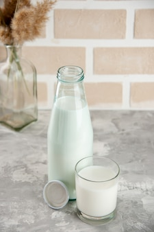 Vista superior da garrafa de vidro e do copo com tampa de leite em um fundo de tijolo de cor pastel