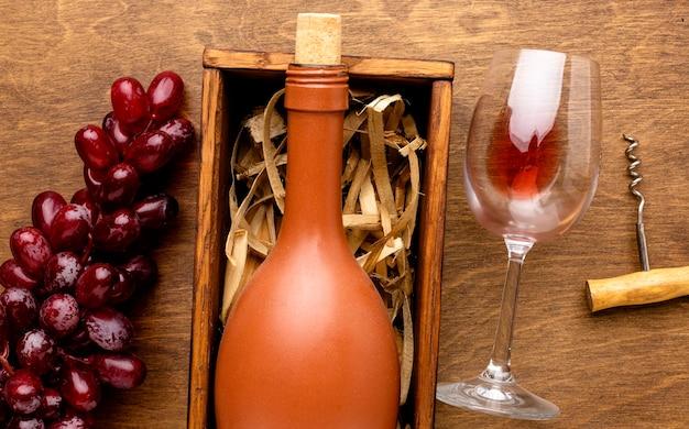 Vista superior da garrafa de vinho e copo com saca-rolhas e uvas