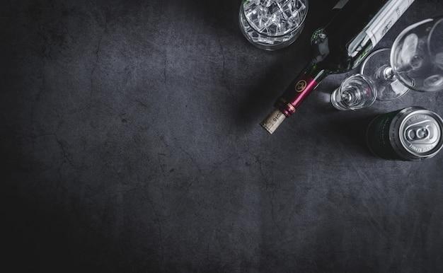 Vista superior da garrafa de vinho, garrafa de vodka, cubo de gelo, cerveja e saca-rolhas