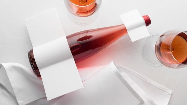 Vista superior da garrafa de vinho transparente e copos com rótulo em branco