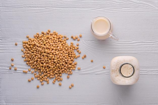 Vista superior da garrafa e jarra de leite de soja na mesa de madeira branca