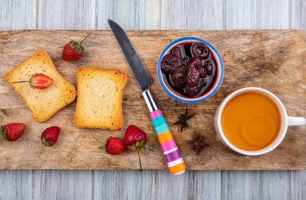 Vista superior da geléia de morango em uma tigela sobre uma placa de cozinha de madeira com faca com fatias de pão torradas com morangos frescos em um fundo cinza de madeira