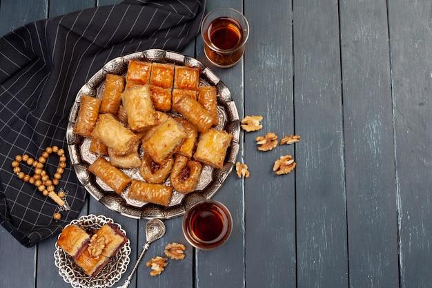 Vista superior da grande bandeja de metal com baklava turco na mesa de madeira planked