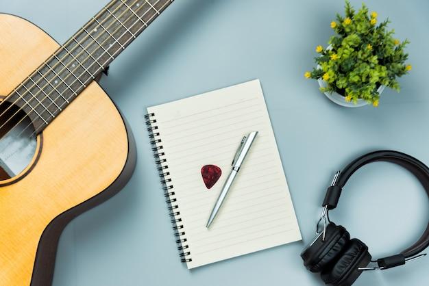 Vista superior da guitarra e caderno e fone de ouvido, conceito de música