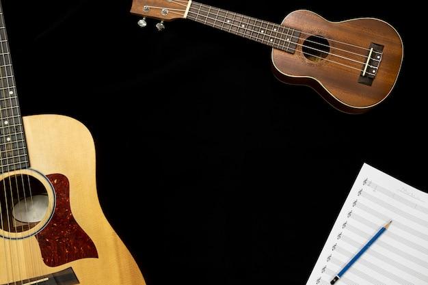 Vista superior da guitarra e ukulele com folha de nota musical sobre o fundo preto