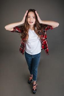Vista superior da jovem aterrorizada com medo de pé e gritando
