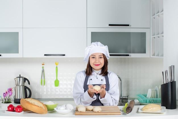 Vista superior da jovem chef feminina sorridente, de uniforme, em pé atrás da mesa, preparando a massa na cozinha branca