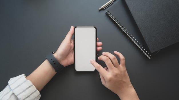 Vista superior da jovem empresária tocando smartphone de tela em branco no espaço de trabalho de luxo escuro