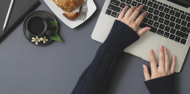 Vista superior da jovem fêmea digitando no computador portátil no espaço de trabalho de inverno com material de escritório