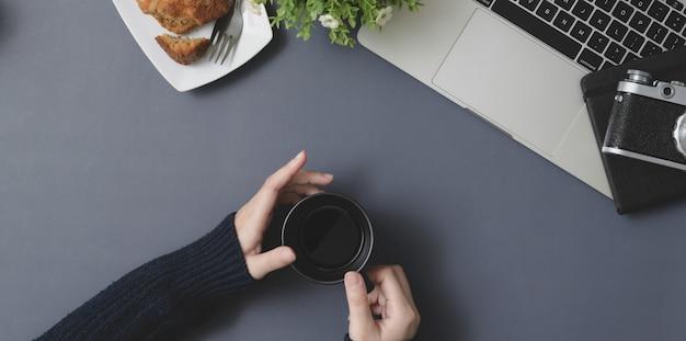 Vista superior da jovem fêmea segurando a xícara de café no espaço de trabalho de inverno com material de escritório