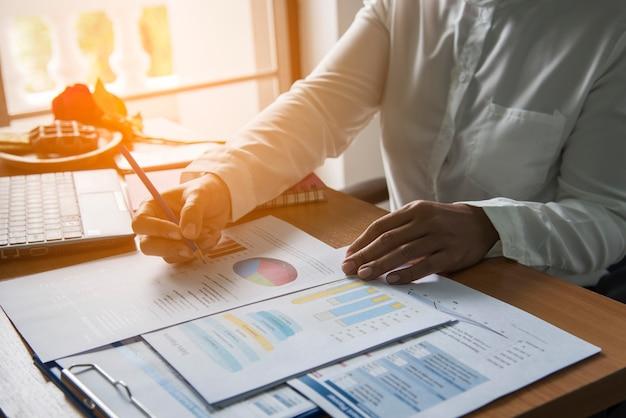 Vista superior da jovem trabalhadora usando laptop e lendo o relatório, gráficos, tabelas, documento no trabalho. mulher de negócios, trabalhando na mesa dela.
