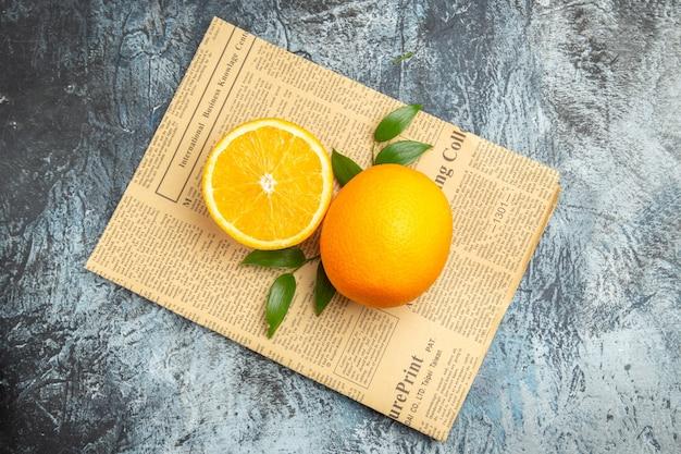 Vista superior da laranja cortada ao meio e inteira com folhas no jornal em fundo cinza