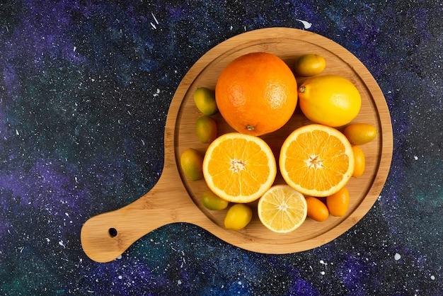 Vista superior da laranja e limão, meio cortada ou inteira sobre uma placa de madeira.